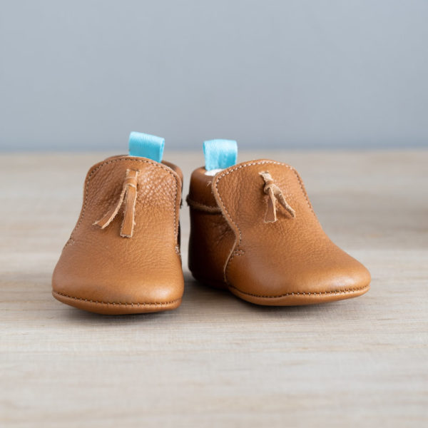 chaussons bébé en cuir souple marron Madeleine avec pompon sur le dessus vu face