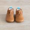 chaussons bébé en cuir souple marron Madeleine avec pompon sur le dessus vu dessus