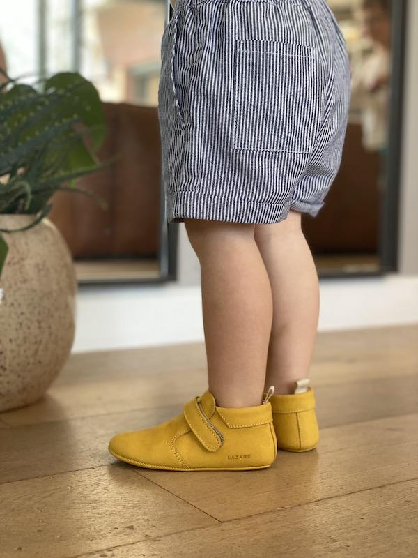 jambes d'enfant portant des chaussons bébé Achille en cuir nubuck jaune souple à scratch