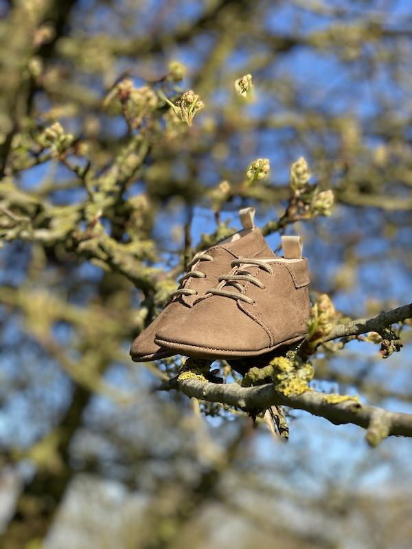 chaussons bébé Colombe cuir souple nubuck taupe avec lacets posés sur une branche d'arbre