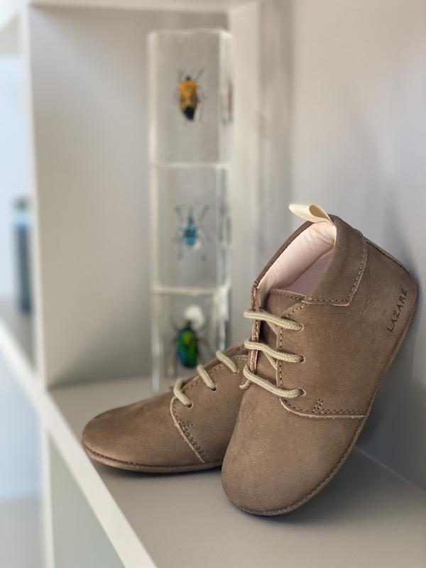 chaussons bébé Colombe cuir souple nubuck taupe avec lacets posés sur une étagère