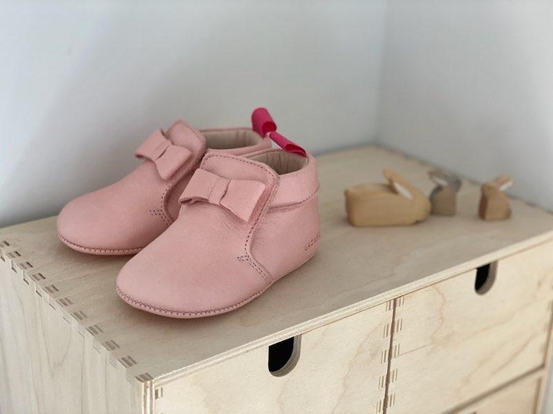 chaussons bébé Arielle en cuir souple rose avec noeud sur le dessus posés sur une étagère en bois