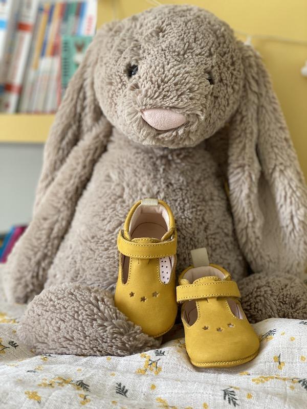 chaussons bébé César en cui nubuck jaune posés devant peluche lapin