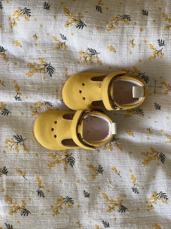chaussons bébé César en cuir nubuck jaune posés sur un foulard