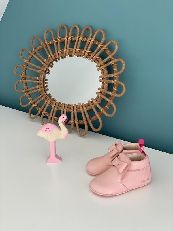 chaussons bébé Arielle en cuir souple rose avec noeud sur le dessus posés devant un miroir