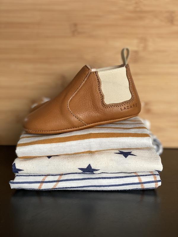 chaussons bébé Oscar en cuir souple marron avec élastique crème de chaque coté de la cheville posés sur une pile de tee-shirts