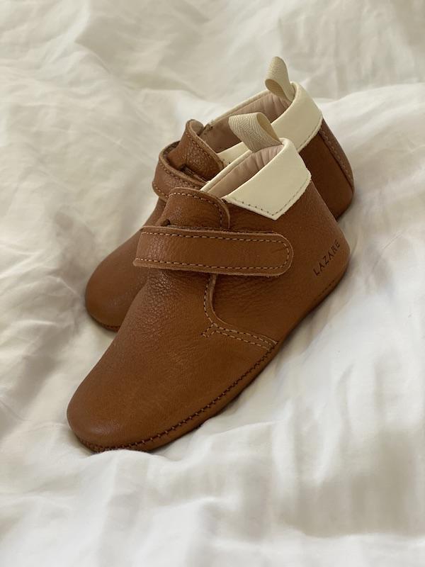 chaussons bébé Achille en cuir souple marron col blanc posés sur une couette