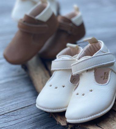 chaussons bébé en cuir souple sur un morceau de bois