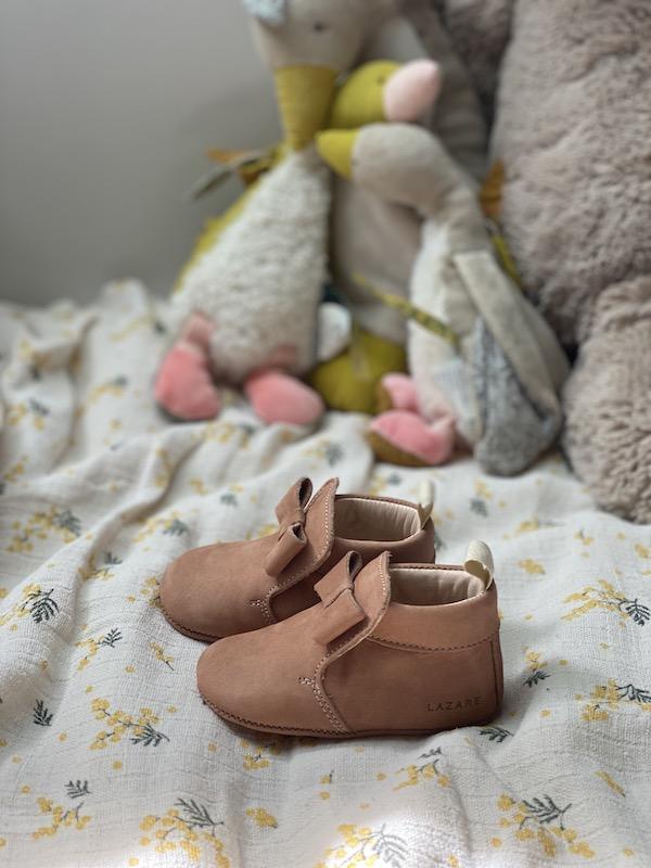 chaussons bébé Arielle en cuir nubuck rose souple avec noeud sur le dessus vu de coté posé sur un lit avec peluches en fond